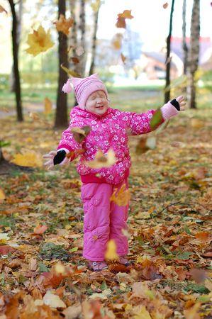 Little girl walks in autumn park photo