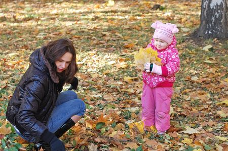 Mum with a daughter walk in autumn park photo