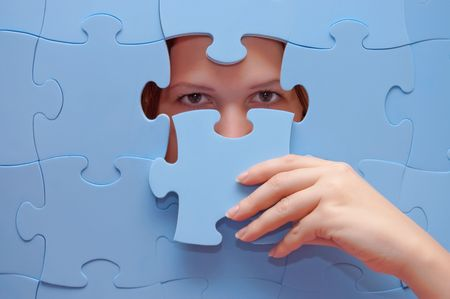 unexpectedness: The girl spies through a blue puzzle
