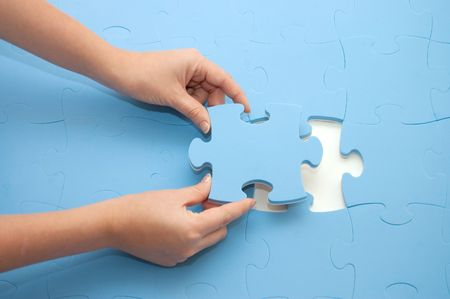 Hand collecting a part of a puzzle Stock Photo - 5960742