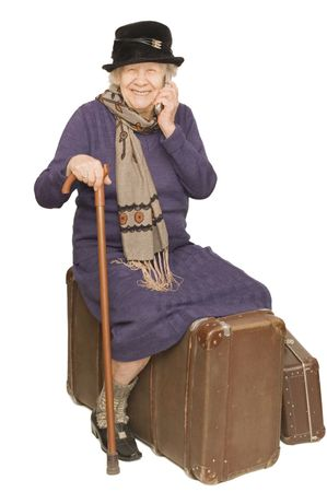 sits: The old lady sits on a suitcase
