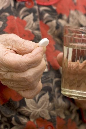 The old woman drinks a tablet Stock Photo