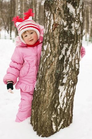 little girl has hidden behind a tree photo