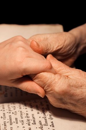 christian women: Old and young hands on the bible Stock Photo