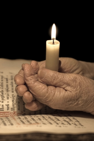 learning pray: Old female hands with a candle Stock Photo