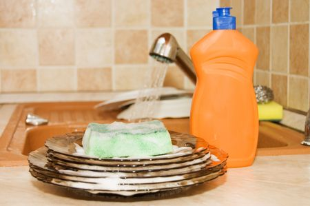 dirty dishes:  Washing-up liquid with a sponge on kitchen