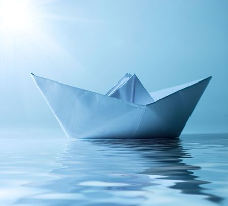 paper boat: concept paper ship in water and sunny blue sky