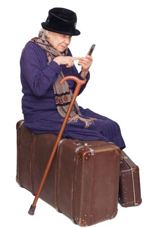 sits: The old lady sits on a suitcase Stock Photo