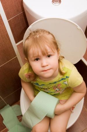 papel higienico: La ni�a se sienta en un inodoro Foto de archivo