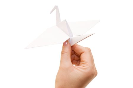 Origami crane in hand isolated on white background Stock Photo - 6667083