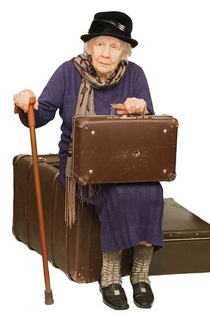 mujer con maleta: La anciana se sienta en una maleta Foto de archivo