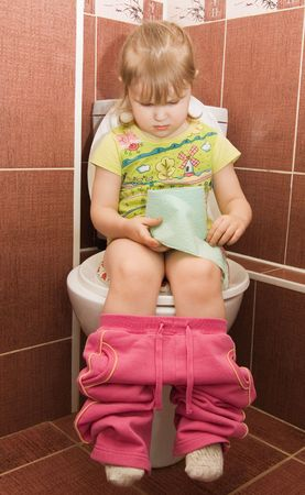 pee: The little girl sits on a toilet bowl