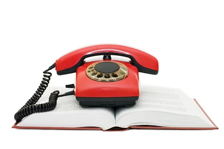 Red phone on the book isolated  photo