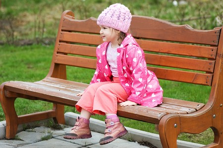 Little girl in park on a bench photo