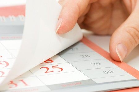 kalender: Die Hand kippt Kalenderblatt