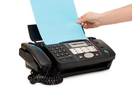 Hand fügt ein Papier in ein fax