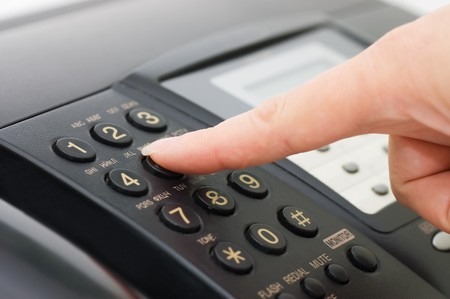 fax: The hand presses the fax button Stock Photo