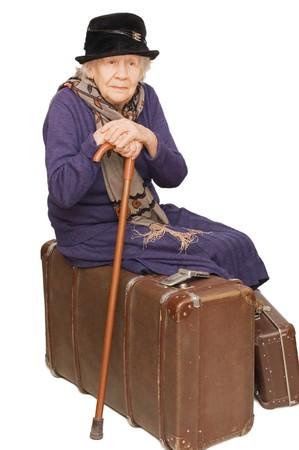 mujer con maleta: La anciana se sienta en una maleta