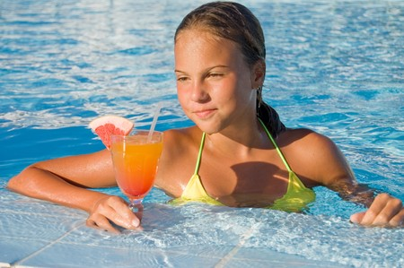 The girl with a cocktail at pool photo
