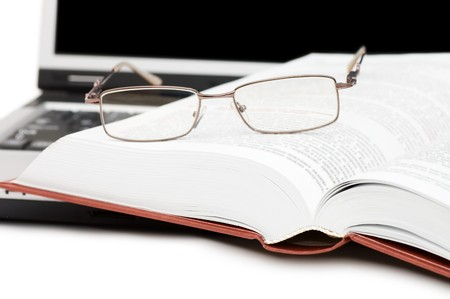 Eyeglasses and books on the laptop  photo