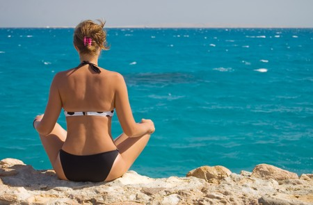 Photograph of a beautiful woman in a sarong meditating on the beach photo
