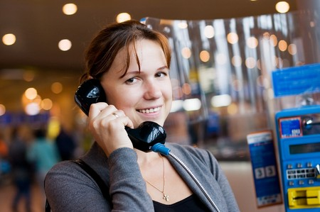 The girl speaks by phone at the airport photo