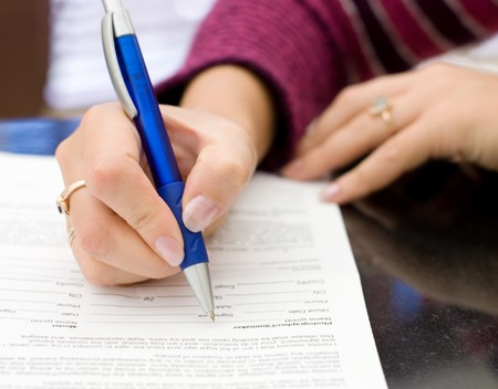 Female hands with a pencil write on a paper Stock Photo - 7970919