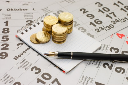 Sheets of a calendar with coins and a notebook photo