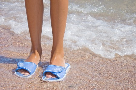 Feet in flip flops at the sea photo