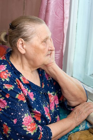 The old woman looks out of the window photo