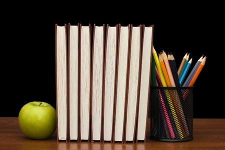 Pila de libros y de manzana en una mesa de madera