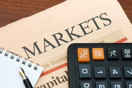 periodicos: El peri�dico con la calculadora en una mesa de madera