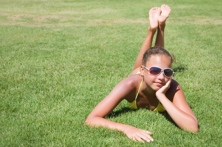 The young girl lays on a grass photo