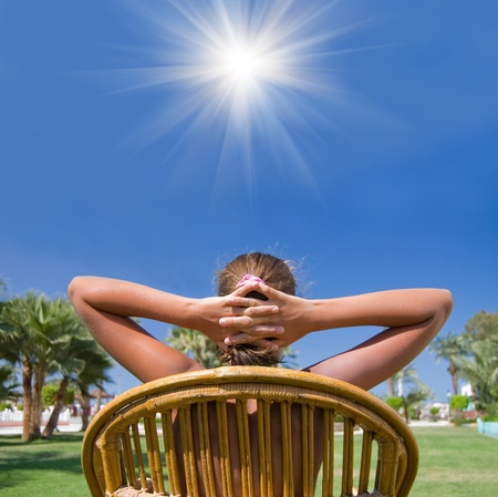 The girl sits in an armchair on a grass  Stock Photo - 8596581