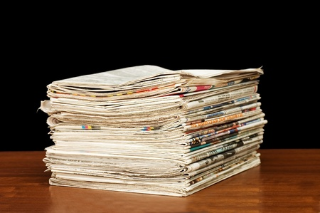 Heap of newspapers on a wooden table  photo