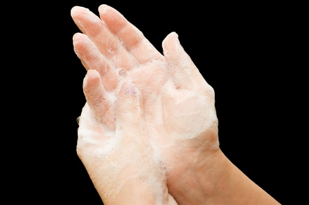Female hands in soapsuds isolated on black photo