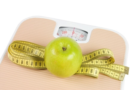 weighing:  Scale, tape and apple on white background