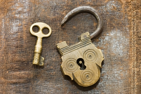 unlock: The old lock and key on a leather background Stock Photo