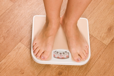 female feet: Female feet on scales Stock Photo