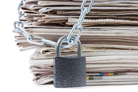 civil rights: pile of newspapers with chains, on white Stock Photo