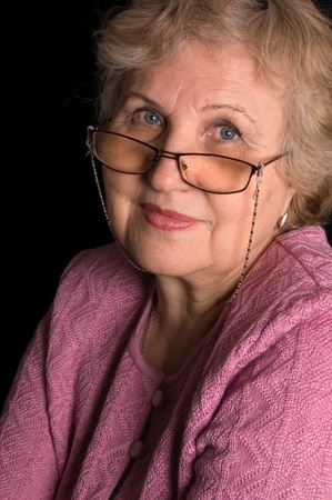 one senior adult woman: The elderly woman on black background Stock Photo