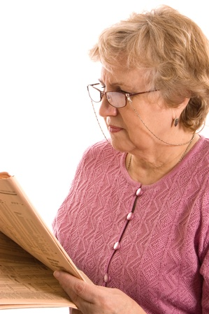 The elderly woman reads the newspaper photo