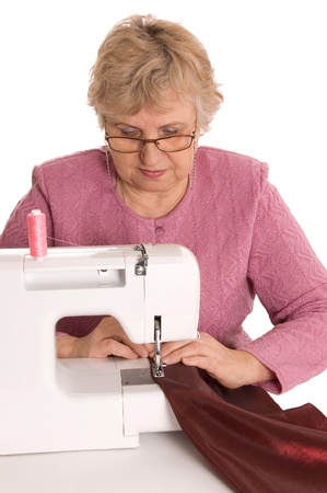 The elderly woman sews on the sewing machine photo