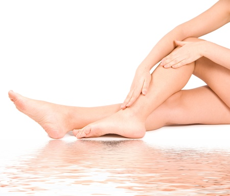 hand rubbing: woman massage feet in water isolated on white background Stock Photo