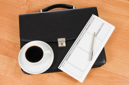 Black portfolio and coffee on a table photo