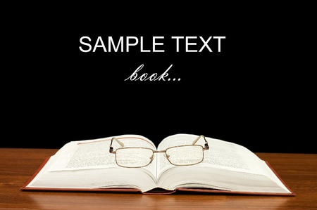 Eyeglasses on books on a wooden table photo