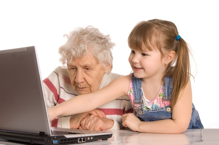 grand kids: The grandmother with the grand daughter at the computer