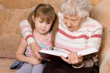 grand daughter: The grandmother with the grand daughter read the book Stock Photo