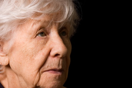 sad old woman: Portrait of the old woman a black background Stock Photo