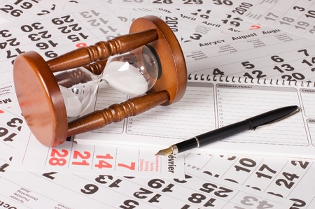 deadline: hourglass on calendar sheets Stock Photo